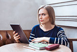 Beautiful girl with the tablet looks suspicious. Woman studying and relaxing being in a cafe.