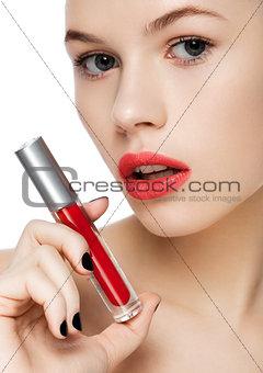 Beautiful girl holding liquid red lipstick tube