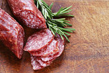 salami sausage with rosemary on a wooden board