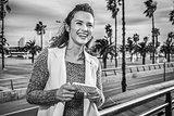 fashion-monger on embankment in Barcelona, Spain writing sms