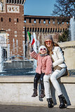 happy mother and daughter tourists in Milan, Italy rising flag