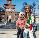mother and daughter travellers near Sforza Castle showing flag