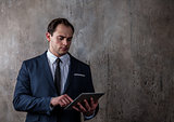 Portrait of a businessman with tablet on concrete gray wall background