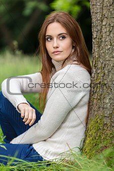 Beautiful Young Woman Sitting Leaning Against Tree