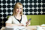 Girl sitting in cafe holds a smartphone