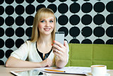Girl sitting in cafe holds a mobile phone
