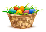 Wicker basket full of Easter eggs on grass