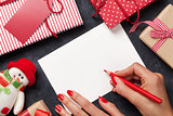 Female writing christmas greeting card and gift wrapping