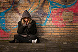 runaway girl sits in front of a wall with graffiti