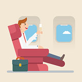 Businessman sitting in an airplane in business class
