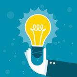 Innovation - hand holds shining light bulb