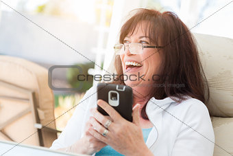 Attractive Middle Aged Woman Laughing While Using Her Smart Phon