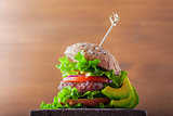 Delicious homemade burger on rustic wooden desk.