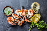 Crabs tentacles with wite wine, lemon, herbs sauce, slate background