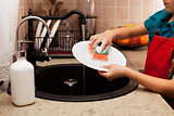 Child washing a plate with sponge at the kitchen sink,