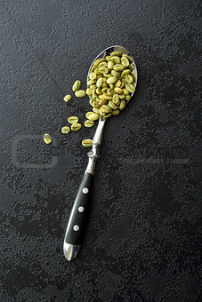 green coffee beans in spoon