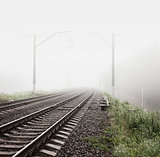 Railway in Fog. Misty Morning Landscape.