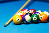 pool billiard balls and cue on the blue cloth table