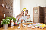 Easter concept. Happy mother and father preparing home decoration with their child for Easter holidays