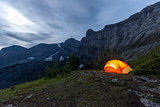 Illuminated tent camping on ridgeline of mountain