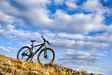 Black bicycle on hill with blue sky background