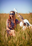 Portrait of lovely young hippie girl with guitar. Shot in the field