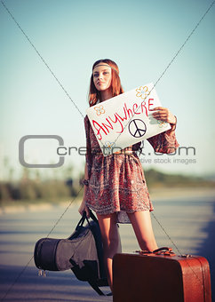 Beautiful young hippie girl hitchhiking on a road