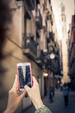 Hand hold a smartphone and make a photo with Santa Maria del Mar Cathedral in Barcelona, Spain