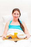 a woman with a tray of breakfast in bed in the morning