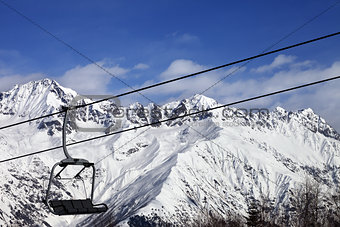 Chair-lift in snow winter mountains at nice sunny day