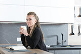 woman in her kitchen reading a book