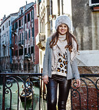 smiling modern traveller woman in Venice, Italy in winter