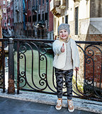modern child in Venice, Italy in winter showing thumbs up
