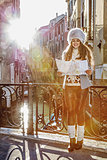 smiling tourist woman in Venice, Italy in winter looking at map