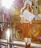 happy young woman in Venice, Italy in winter with map