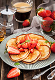 Homemade delicious pancakes served with fresh strawberries and h