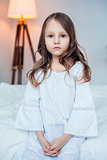 Cute little girl wearing nightgown sitting on the bed.