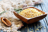 Italian pasta orzo in a wooden bowl.