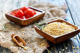 Wooden bowls with orzo pasta and canned tomatoes.