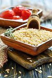 Orzo pasta and wooden scoop in bowl close-up.