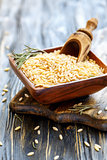 Wooden scoop in bowl of orzo pasta.