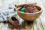 Wooden bowl and scoop with cocoa powder.