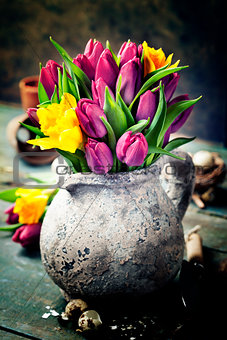 Beautiful spring tulips bouquet, easter eggs and garden tools