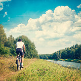 Man Riding a Bike on River Bank. Nature Background