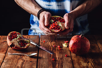 Opened Pomegranate in the Hands.