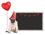 cute pug puppy dog with red party hat, sitting next to blank blackboard sign and holding heart shaped balloon, isolated on white background