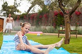 Father And Daughter Having Fun On Water Slide In Garden