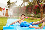 Father And Son Having Fun On Water Slide In Garden