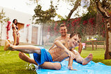 Family Having Fun On Water Slide In Garden