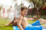 Family Having Fun On Water Slide In Garden